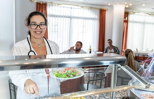 Lady making a salad at food counter